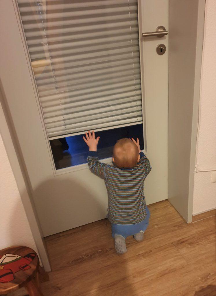 Kleinkind schaut durch das Glas einer Innentüre